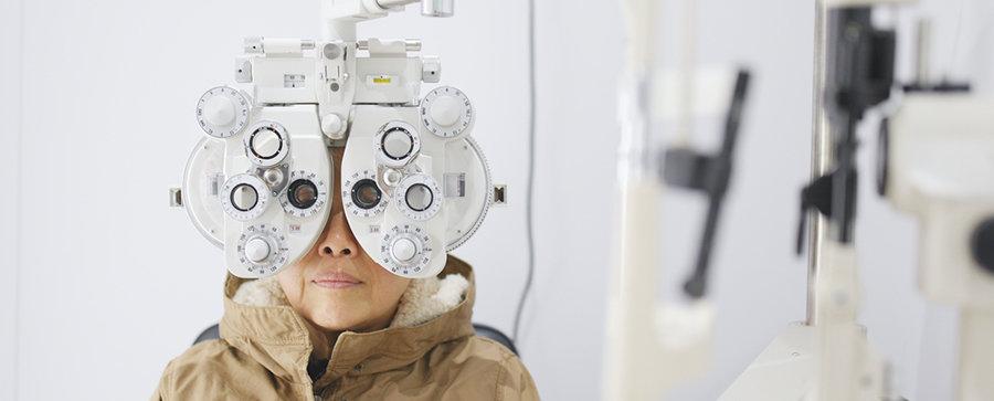 Older woman taking eye exam vision test